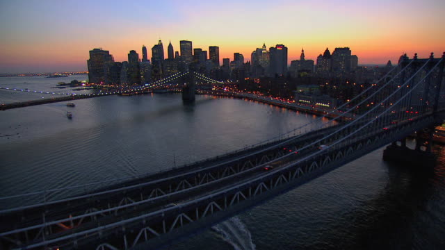 AERIAL East River and city skyline at dawn, with red, orange, and yellow striping the horizon sky / New York City, New York, United States