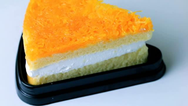 Eating a slice of orange cake.