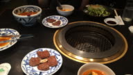 Eating dinner in nice traditional restaurant in Tokyo with food and grill in table during travel vacations in Japan.