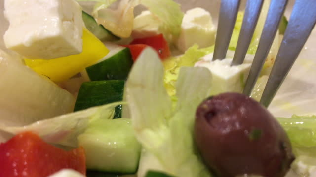 Eating Greece Salad with Fork, Olive, Lettuce, Cucumber, Cheese, Tomato
