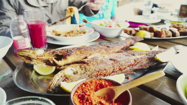 Eating Grilled Fish in Restaurant