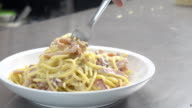 Eating spaghetti carbonara.