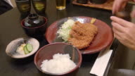 Eating Tonkasu with rice and soup in Tokyo, Japan