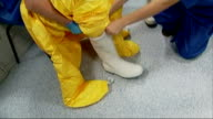 Preparations at Halamshire Hospital ENGLAND Sheffield Royal Hallamshire Hospital INT Hospital bed / medical worker putting yellow protective suit and...