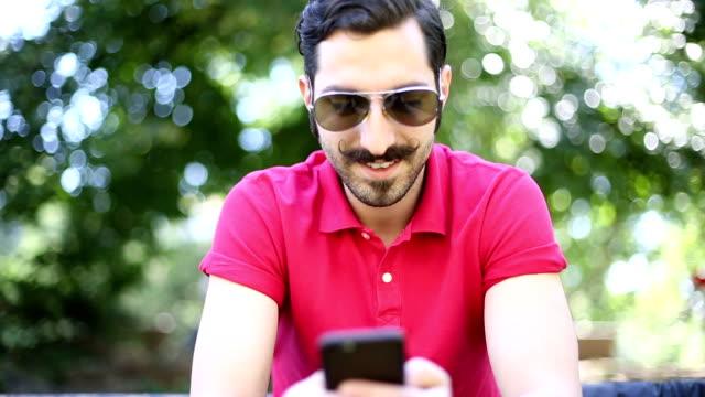 Eccentric man texting on smart phone
