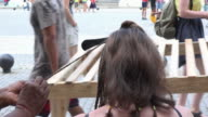 Economic changes in Havana, Cuba: tourist getting a hairdo in the Old Plaza from a private small business owner.