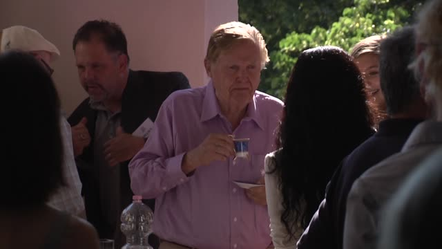Economist Robert Mundell greeting guests in his Italy home / speaking at conference with other economists and bankers in his living room of his...