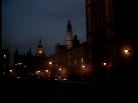 Autumn Financial Statement ENGLAND London Houses of Parliament GV Houses of Parliament as street lights blazing MS Light shining from upper storey...