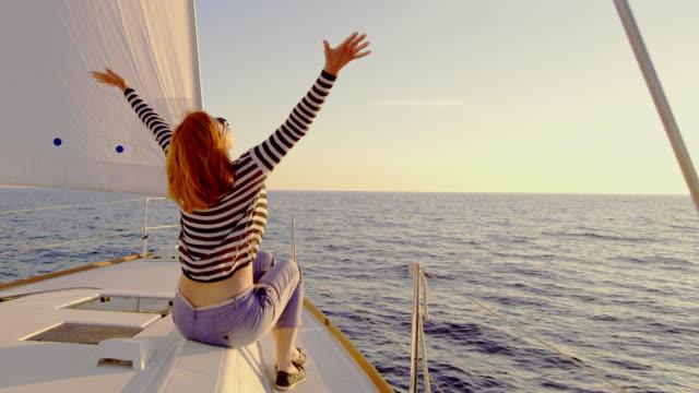 SLO MO extatische vrouw genieten van het zeilen bij zonsondergang