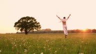 WS Ecstatic young man running through a meadow at sunset
