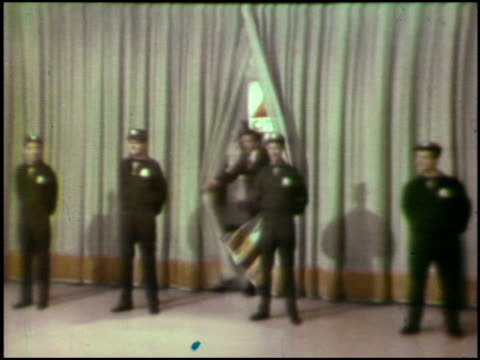 / Ed McMahon is introduced as the emcee / Ed appears from behind curtain / Ed nods to acknowledge singing group The Four Lads who are dressed as...