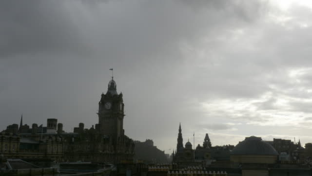 T/L WS Edinburgh, Scotland skyline, approaching storm, clock tower of Balmoral Hotel at Waverley Station in foreground