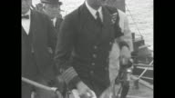 Edward Prince of Wales walks up gangplank to ship he wears naval uniform with white trousers / Prince salutes as he stands on platform behind a large...