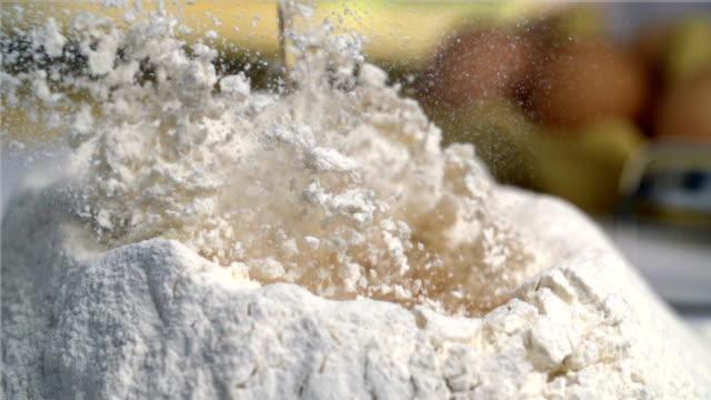 Egg falling into flour