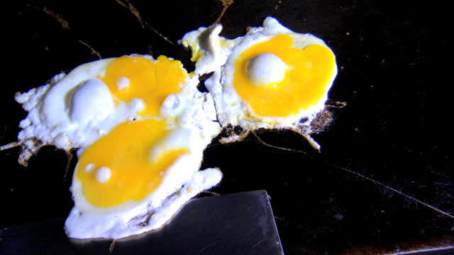 Eggs frying on flat frying surface in unidentifiable kitchen unidentifiable hand w/ metal spatula separating an egg flipping all eggs over Breakfast...