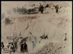 Egyptian ruins / Workers at dig site / Carts of rubble dumped / children in mouth of tomb