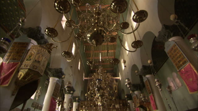 Elaborate candelabras and incense holders are suspended from the central nave in Saint Catherine's Monastery. Available in HD.