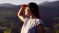 Elated woman enjoying sunset in mountains