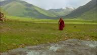 Elderly Buddhist monk walks beside river, Tibet Available in HD.