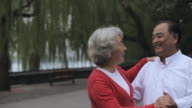MS Elderly couple dancing together in park/ Beijing, China