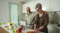 Elderly couple preparing a meal together