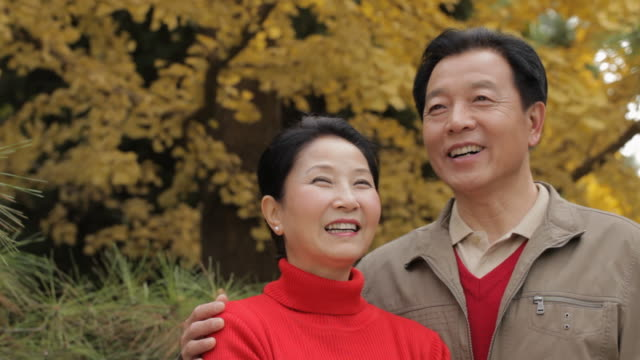 CU Elderly couple smiling and looking at each other, standing in park / China
