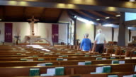 WS TS elderly couple walking through empty catholic church alongside pews through center aisle and approaching altar and genuflecting