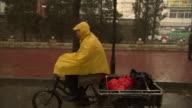 MS TS Elderly man in rain poncho riding three-wheeled bike with truck bed, Beijing, China