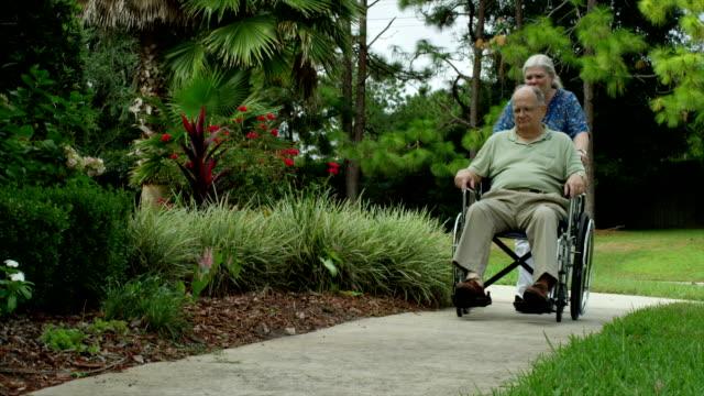 Älterer Mann im Rollstuhl mit Krankenschwester