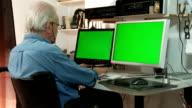 elderly man in wheelchair working at a computer