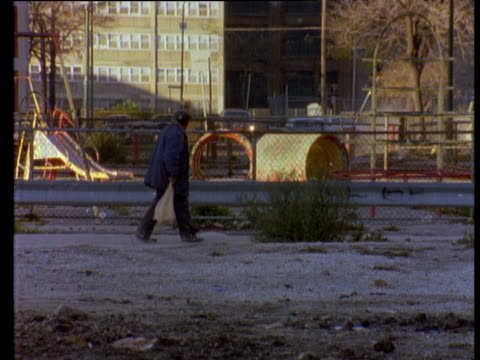 Elderly man passes mothers with children walking along street wearing warm jackets through urban ghetto playground in background