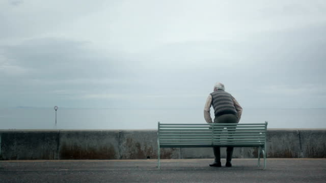 Elderly (Senior) man sits by the seaside