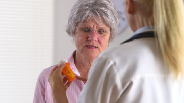 Elderly patient asking doctor about prescription medicine
