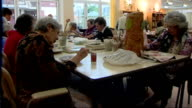 INT Elderly people taking part in art class in care home woman's hands using sellotape old woman knitting at table and residents at care home...