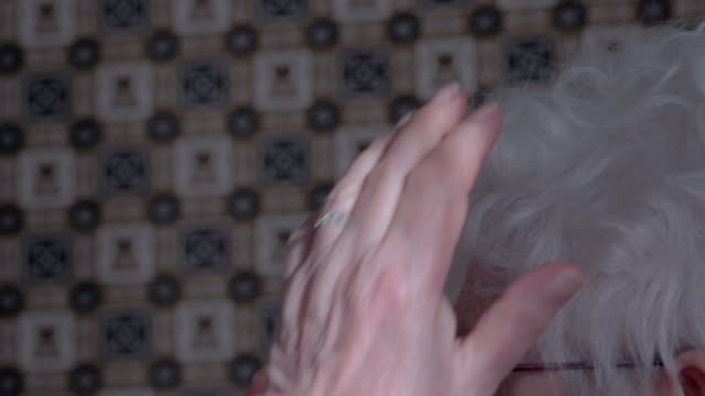 Elderly woman arranging her hair