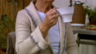 Elderly woman drinking coffee and using a mobile phone Stockholm Sweden.