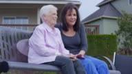 Elderly woman enjoying the outdoors with her caregiver/daughter