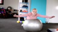 Elderly woman exercising on fitness ball
