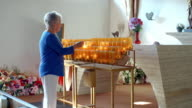 MS TS elderly woman lights votive candle with a match lighted by another prayer candle in votive candle rack inside catholic church