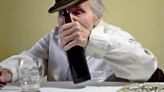 Elderly woman opens bottle of dark beer.