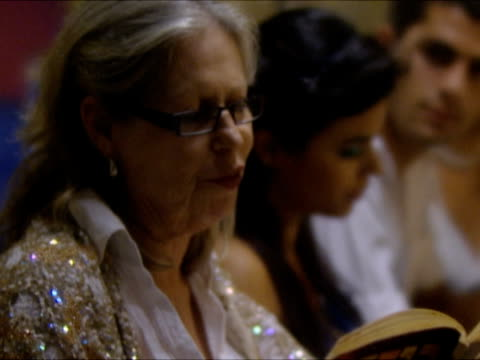 CU TU SELECTIVE FOCUS Elderly woman reading from prayer book, sitting at dinner table at Seder Night during Passover / Beit Yitzhak, Israel