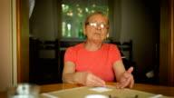 Elderly woman talking at camera