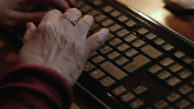 Elderly woman typing at computer