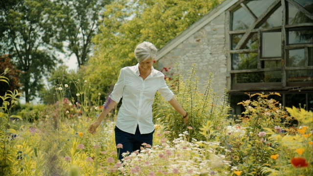 Elderly woman walking through garden and smelling on flower