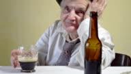 Ältere Frau mit Glas von dunklen Bier.