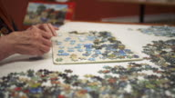 Elderly woman working on a jigsaw puzzle