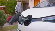 SLO MO Electric car charging while family enters their house