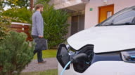 SLO MO Electric car charging while man enters the house