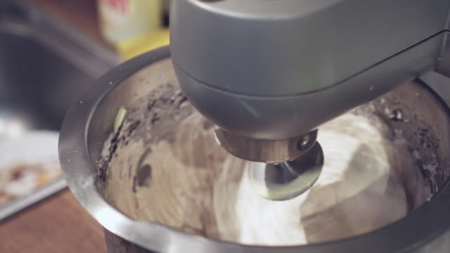 Electric mixer machine whipping cream in metal bowl