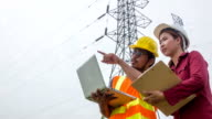 HD CRANE : Electric worker and engineer discuss with laptop and clipboard